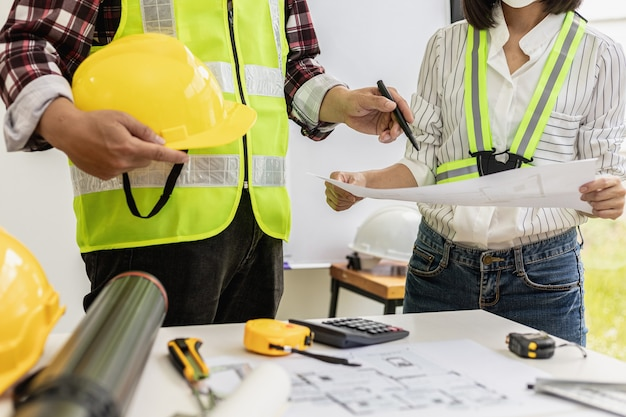 Architekt ingenieure stehen bereit, um sich die entwürfe der entworfenen häuser anzuschauen, sie treffen sich zusammen, um den bau zu planen und einige der entwürfe zu ändern. design- und einrichtungsideen.