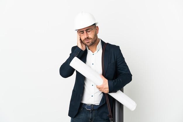 Architekt mann mit helm und blaupausen isoliert auf weißem hintergrund mit kopfschmerzen