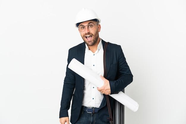 Architekt mann mit helm und hält blaupausen lokalisiert auf weiß mit überraschendem gesichtsausdruck