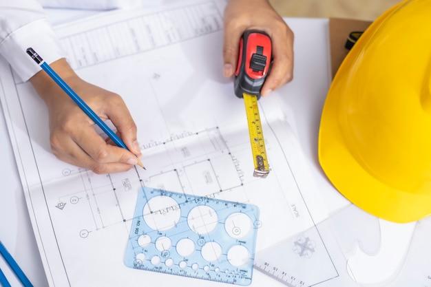 Architekt oder ingenieur, der im büro am arbeitsplatz für architekturplan arbeitet