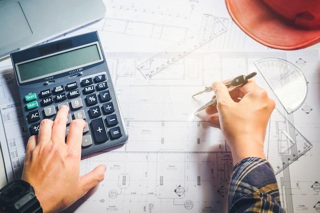 Architekt oder ingenieur, die im büro auf plan arbeiten. architekten arbeitsplatz