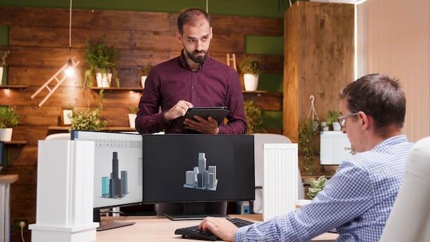 Architekt sitzt in seinem büro und erklärt seinem kollegen das gebäudekonzept