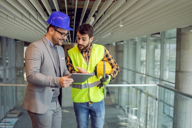 Architekt und bauarbeiter stehen im gebäude im bauprozess und betrachten blaupausen auf tablette