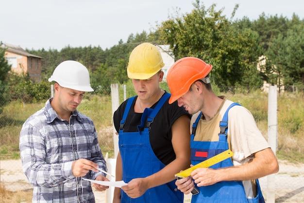 Architekt und bauherren diskutieren spezifikationen, während sie auf einer baustelle um ein handheld-dokument gruppiert stehen
