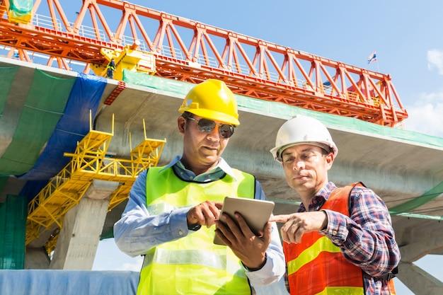 Architekt und ingenieur arbeiten zusammen mit digital wireless tablet