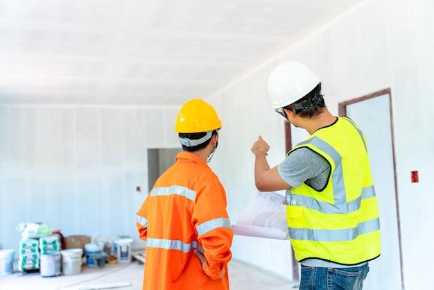 Architekt und ingenieur mit vorarbeiter inspizieren den bau der wohnsiedlung auf den erfolgreichen bauplan, bevor sie qualitätswohnungen an die kunden auf der baustelle senden