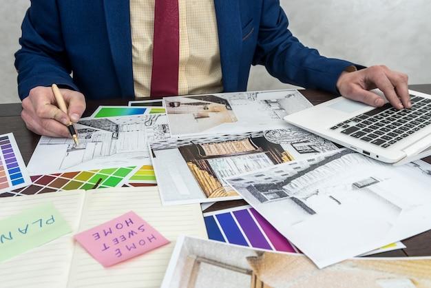 Architekten hände zeichnen moderne wohnungen mit farbmuster und laptop auf kreativem schreibtisch, büro. mann, der farben für raumdekoration wählt