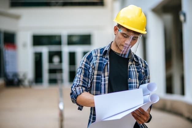 Architekten halten den bauplan und überprüfen die arbeit.