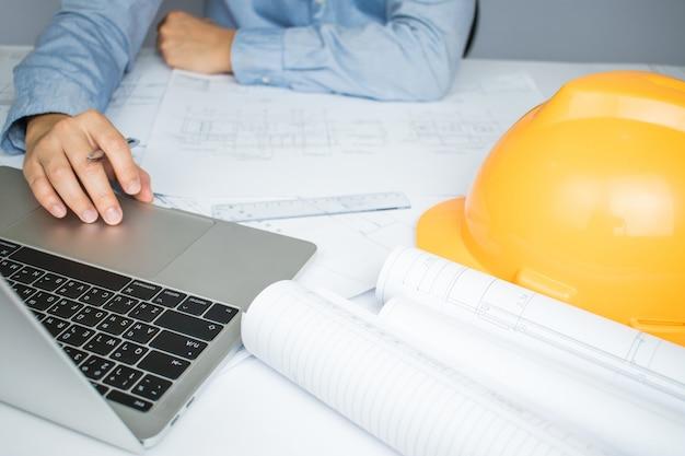 Architekten nutzen den laptop häufig für informationen zu blueprint-papier auf dem tisch.
