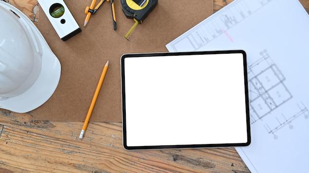 Architektenarbeitsplatz mit digitaler tablette, blaupause und schutzhelm auf holztisch.