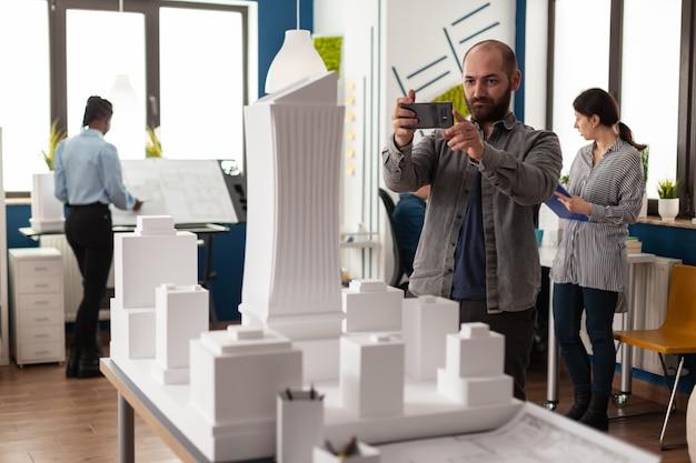 Architektenberufsmann, der das maquette-layout betrachtet