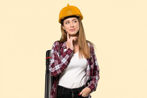 Architektenfrau, die eine idee beim auf gelb oben schauen denkt