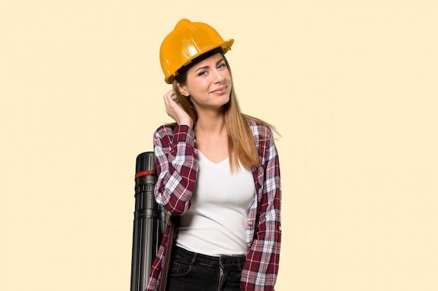 Architektenfrau, die eine idee beim verkratzen des kopfes über lokalisierter gelber wand denkt
