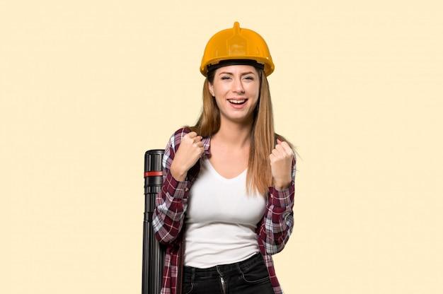 Architektenfrau, die einen sieg in siegerposition über lokalisierter gelber wand feiert