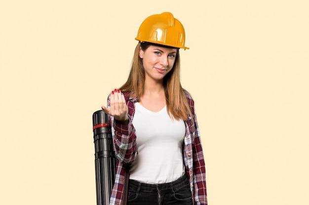 Architektenfrau, die einlädt, mit der hand zu kommen. freut mich, dass du auf gelb gekommen bist
