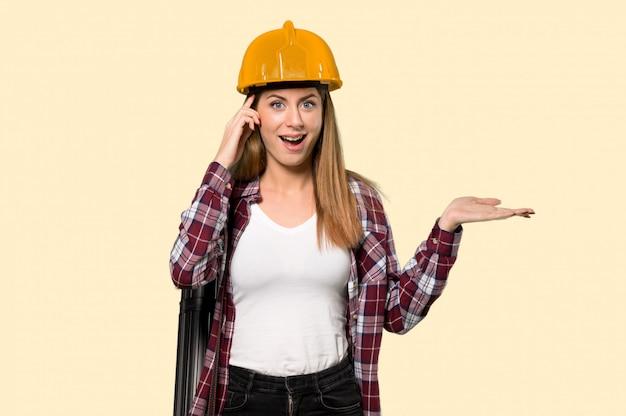Architektenfrau, die finger auf die seite über lokalisiertem gelb überrascht und gezeigt worden sein würden