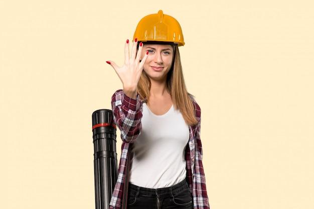 Architektenfrau, die fünf mit den fingern über lokalisierter gelber wand zählt