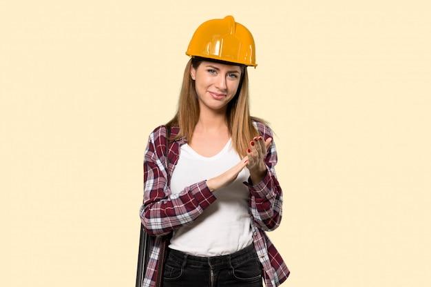 Architektenfrau, die nach darstellung in einer konferenz auf gelb applaudiert
