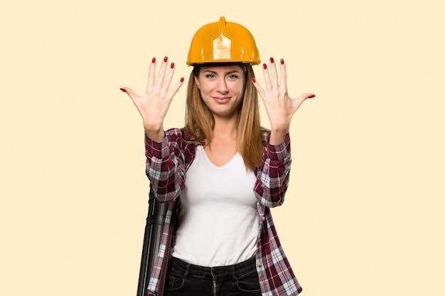 Architektenfrau, die zehn mit den fingern auf gelb zählt