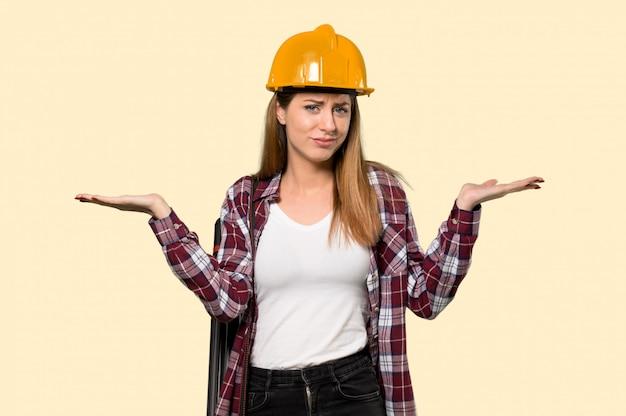Architektenfrau, die zweifel beim anheben von händen auf gelb hat