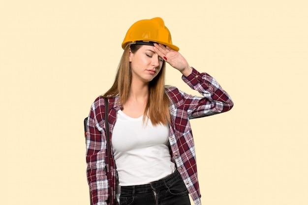 Architektenfrau mit müdem und krankem ausdruck auf gelb
