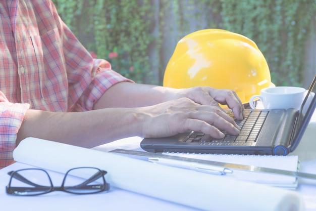Architekteningenieur, der laptop für das arbeiten mit sturzhelm, laptop und kaffeetasse verwendet