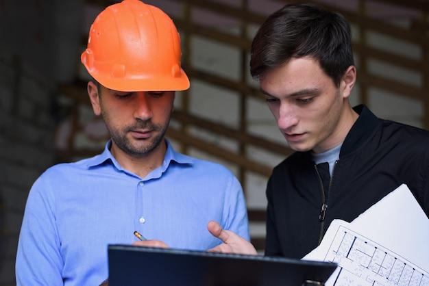 Architekteningenieur, der orange sturzhelm am arbeitsstandort erklärt dem kunden die projektpläne trägt
