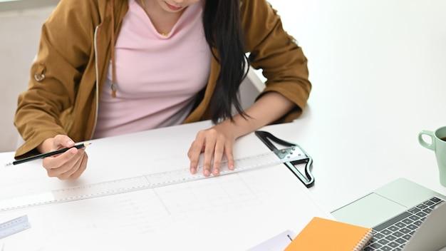 Architekteningenieurbehälter und machthaberskala auf dem schreibtisch mit einem plan im büro.