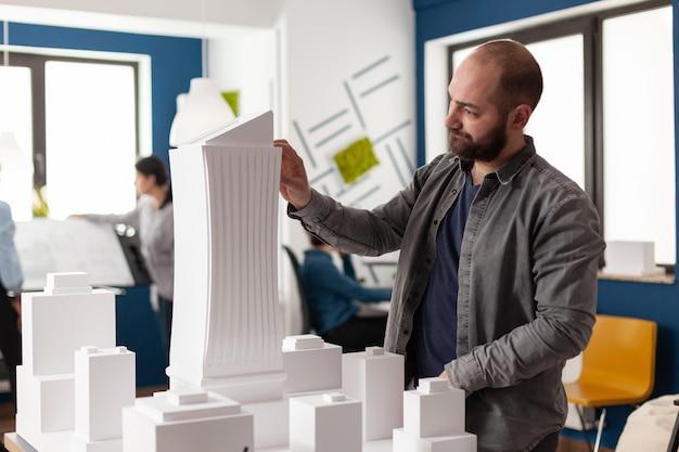 Architektenmann, der design im berufsbüro betrachtet