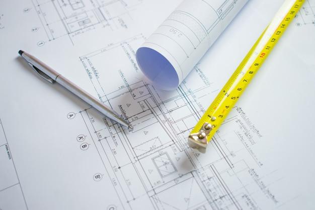 Architektenschreibtisch mit stift, messinstrumentpatrone auf dem plan für das haus.