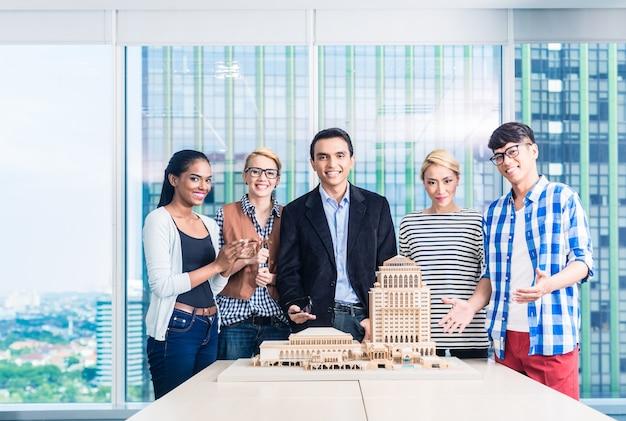 Architektenteam präsentiert modellbau in präsentation beim kunden