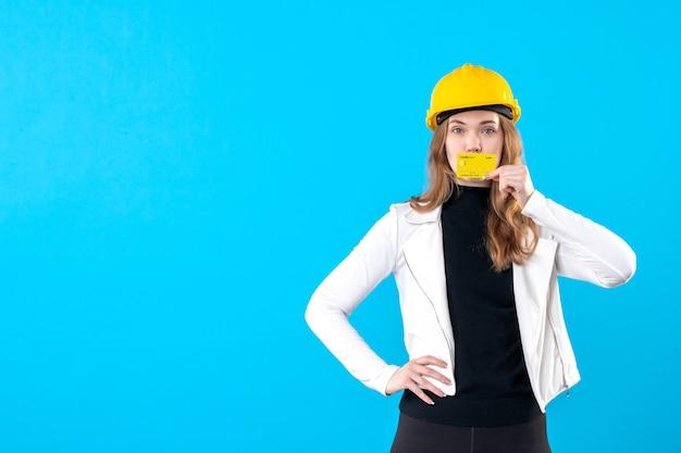 Architektin der vorderansicht, die bankkarte auf blau hält