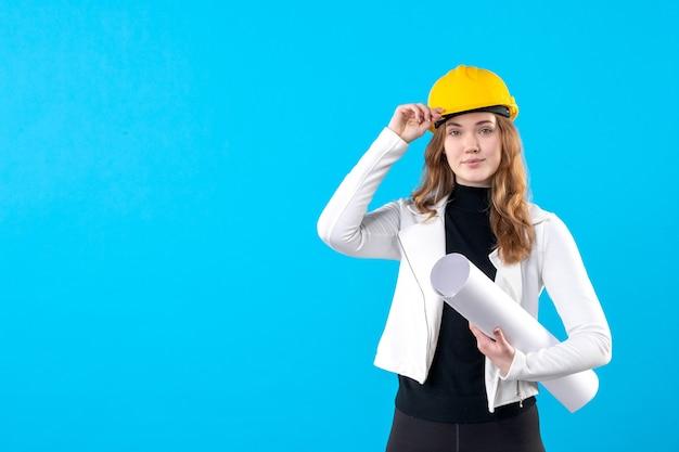 Architektin der vorderansicht im gelben helm, der plan auf blau hält