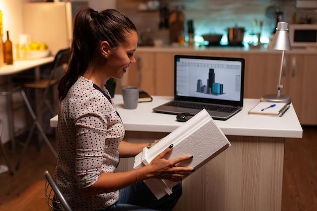 Architektin, die sich das gebäudemodell während der späten nachtzeit im home office ansieht
