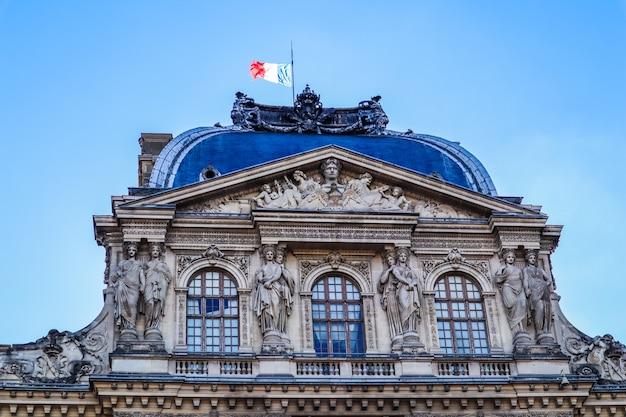 Architektonische details des louvre-palastes mit der französischen flagge paris frankreich