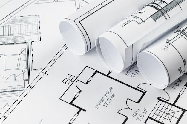 Architektonische konstruktionszeichnungen zu einer rolle verdreht, bauprojekte auf papier.