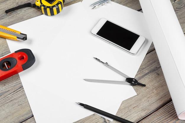 Architektonische zeichnungen. instrumente auf dem arbeitstisch. leeres blatt papier