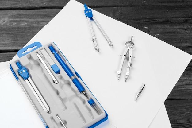 Architektonische zeichnungen. instrumente auf dem arbeitstisch. platz für text. leeres blatt papier