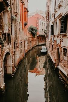 Architektur und wahrzeichen von venedig, italien. alte backsteingebäude und beige gebäude, enge gassen zwischen den häusern, ziegeldächer.