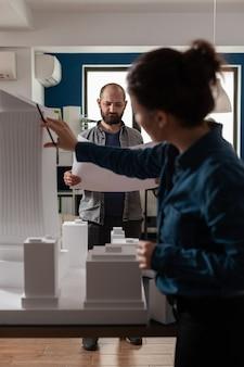 Architekturarbeiter, die blaupausen mit maquette-gebäudemodell überprüfen