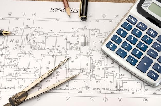 Architekturbauunterlagen mit stift und taschenrechner