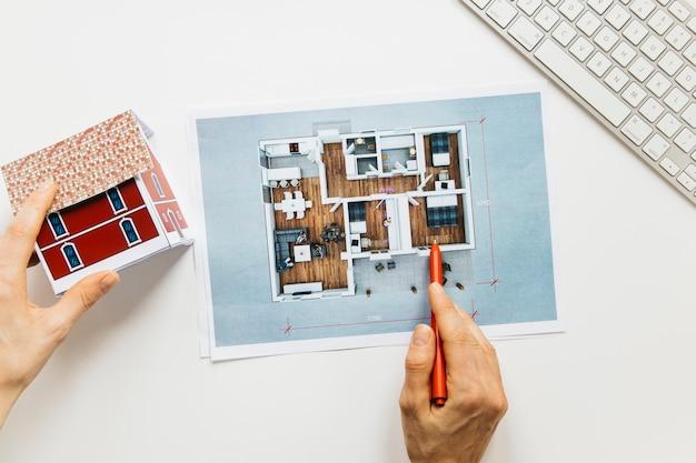 Architekturhand, die hausmodell bei der prüfung der blaupause hält