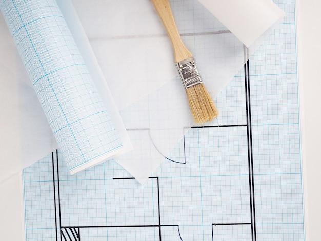 Architekturzeichnungen für den grundriss des wohnungsentwurfs, millimeterpapier, transparentpapier in der rolle und bleistifte.