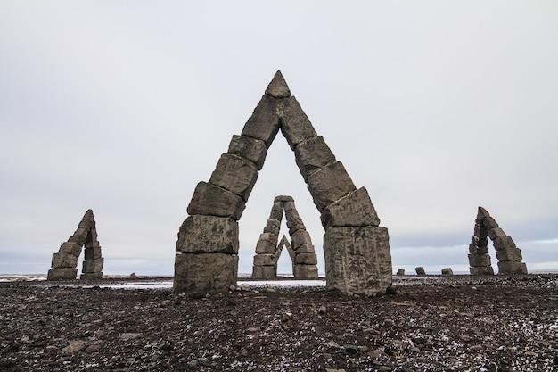 Arctic henge, umgeben von einem schneebedeckten feld unter einem bewölkten himmel in island