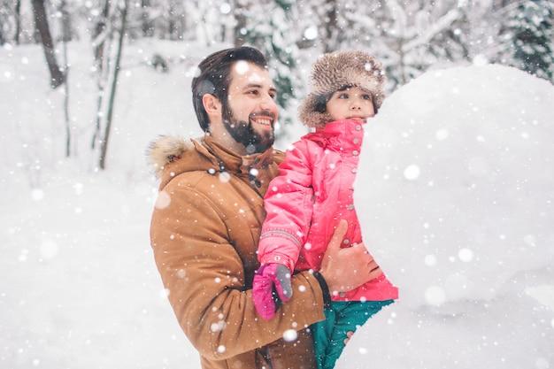 Arenthood-, mode-, jahreszeit- und leutekonzept - glückliche familie mit kind im winter kleidet draußen