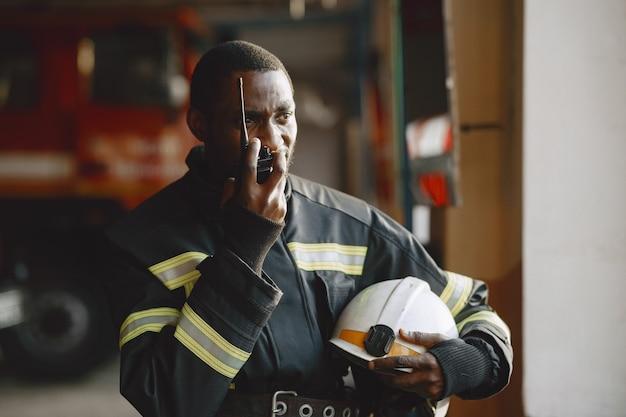 Arfican feuerwehrmann in uniform. mann bereitet sich auf die arbeit vor. guy benutzt einen funksender.