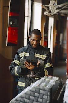 Arfican feuerwehrmann in uniform. mann bereitet sich auf die arbeit vor. kerl mit tablette.