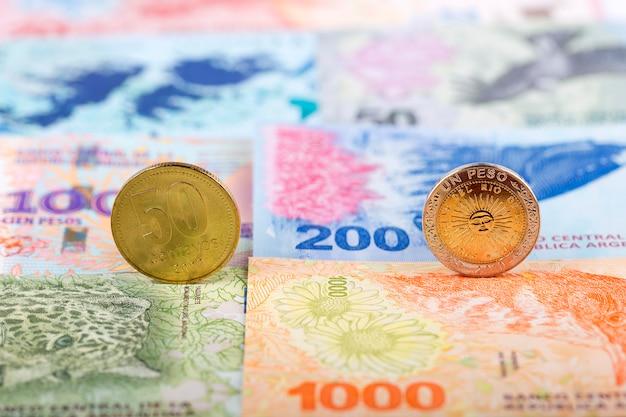 Argentinische münzen auf dem hintergrund von banknoten