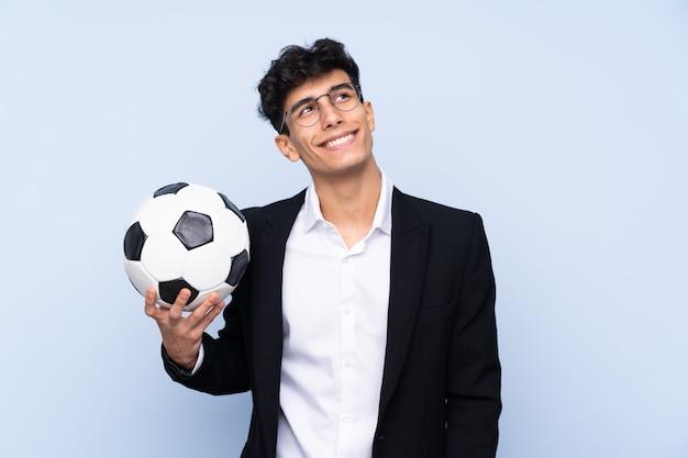 Argentinischer fußballtrainer über der lokalisierten blauen wand, die oben beim lächeln schaut