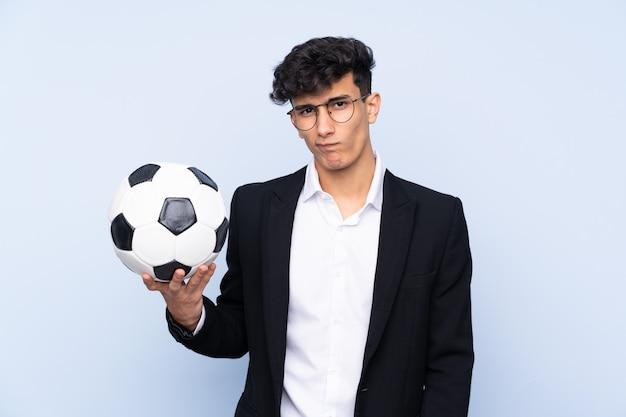 Argentinischer fußballtrainer über lokalisierter blauer wand mit traurigem ausdruck